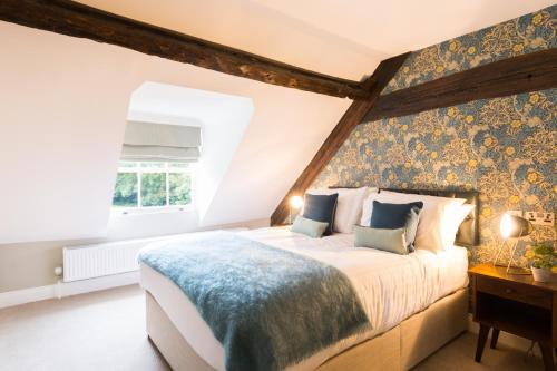 A bed or beds in a room at Hallgarth Manor House