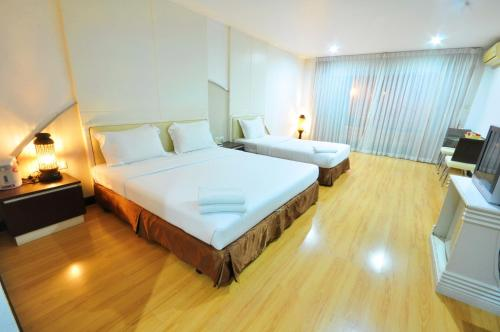 A bed or beds in a room at The Great Hotel Hatyai