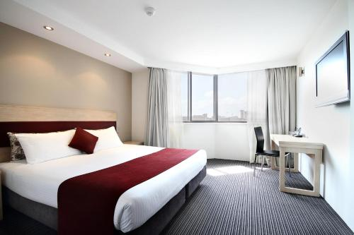 A bed or beds in a room at Central Studio Hotel Sydney