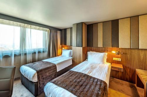 A bed or beds in a room at All Seasons Residence Hotel