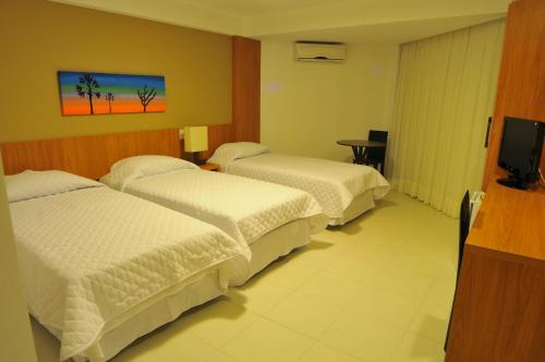 A bed or beds in a room at Garbos Trade Hotel