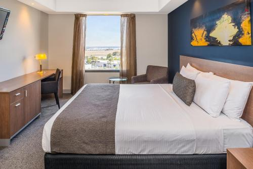 A bed or beds in a room at Mantra Tullamarine Hotel