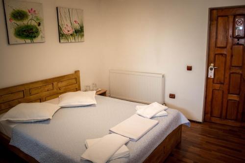 Un pat sau paturi într-o cameră la Pensiunea Bujorul