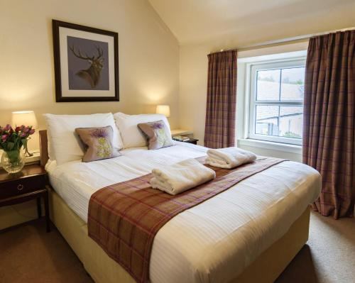 A bed or beds in a room at Loch Leven Hotel & Distillery