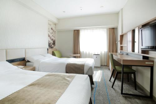 A bed or beds in a room at Sapporo Tokyu REI Hotel