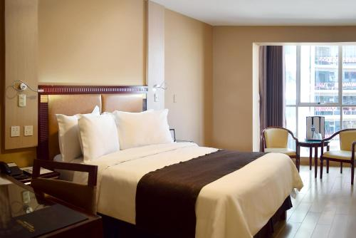 A bed or beds in a room at Gran Mundo Hotel & Suites
