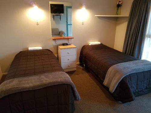 A bed or beds in a room at Camberley Court Motel