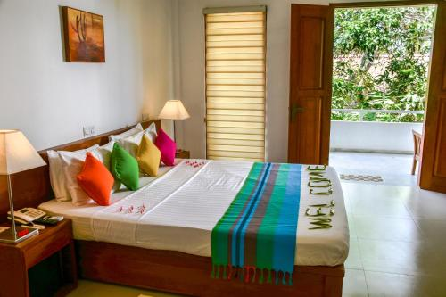 A bed or beds in a room at The Residence Hikkaduwa