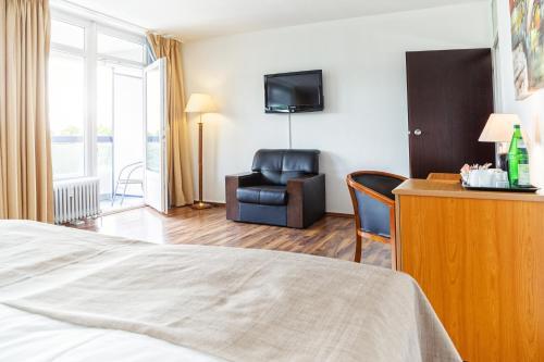 Телевизор и/или развлекательный центр в Hotel Plöner See by Tulip Inn