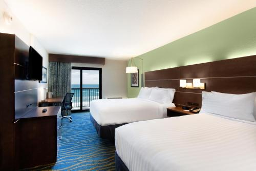 A bed or beds in a room at Holiday Inn Express & Suites Oceanfront Daytona Beach Shores, an IHG Hotel