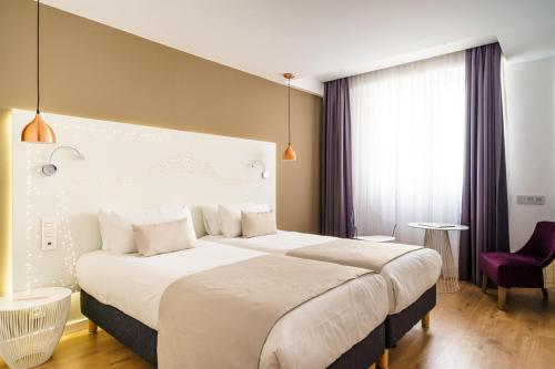 A bed or beds in a room at The Walt Madrid