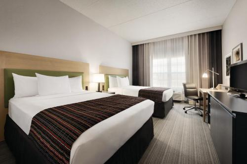 A bed or beds in a room at Country Inn & Suites by Radisson, Coralville, IA