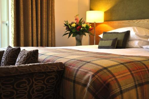 A bed or beds in a room at Craigmhor Lodge & Courtyard