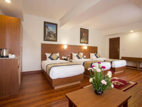 A bed or beds in a room at Oasis Kathmandu Hotel