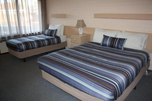A bed or beds in a room at Raglan Motor Inn