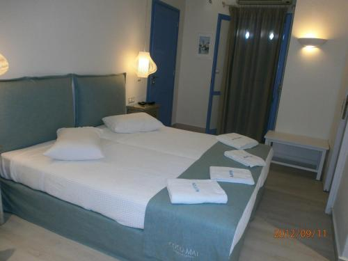A bed or beds in a room at Alkyoni Beach Hotel