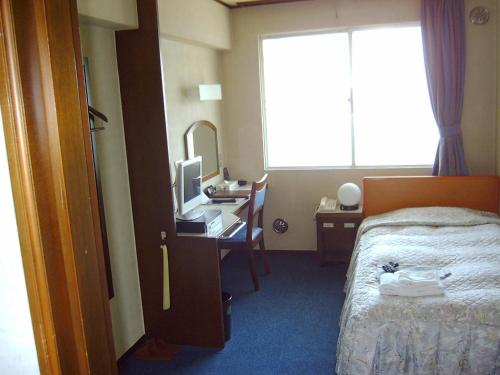 A bed or beds in a room at Tokyo Business Hotel