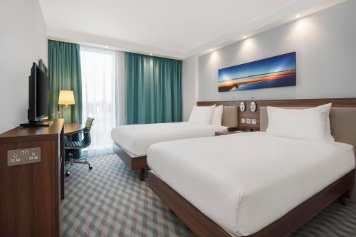 A bed or beds in a room at Hampton By Hilton London Stansted Airport