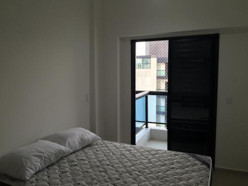 Cama ou camas em um quarto em Flat Guarujá