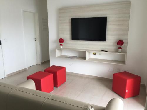 Uma TV ou centro de entretenimento em Flat Guarujá
