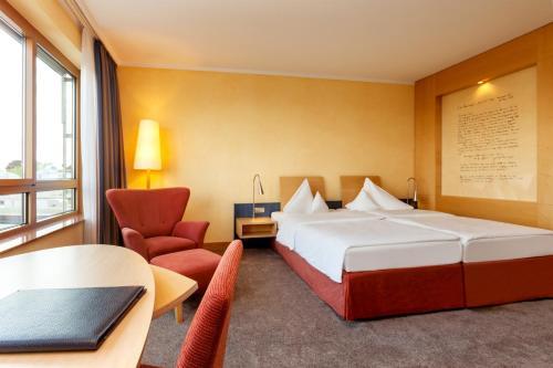Een bed of bedden in een kamer bij Vienna House Remarque Osnabrück