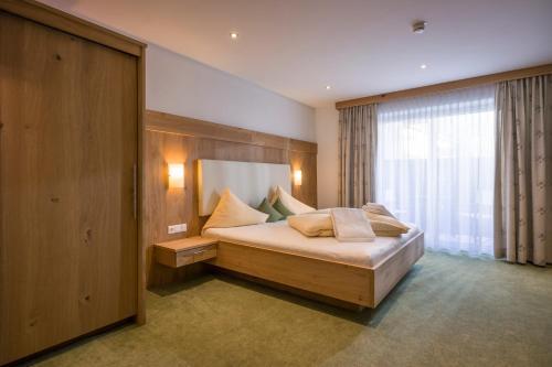 A bed or beds in a room at Alpenhof Hotel Garni Suprême