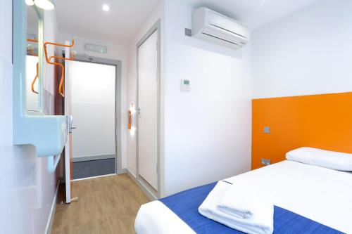 A bed or beds in a room at easyHotel London Luton