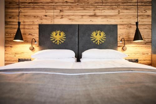 A bed or beds in a room at Der Postwirt - Alpen LifeStyle mit Tradition