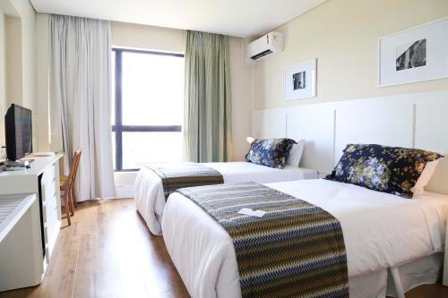Кровать или кровати в номере Vitória Hotel Convention Paulínia