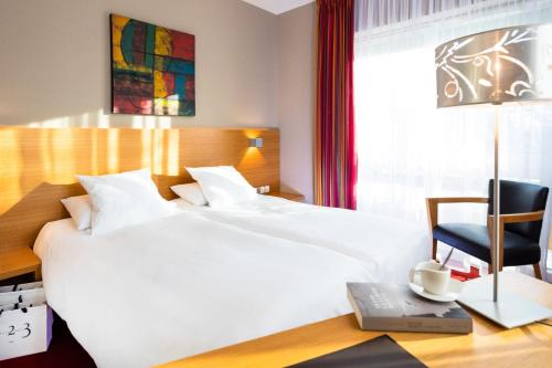 A bed or beds in a room at Auberge Sundgovienne