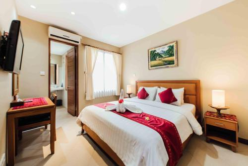 A bed or beds in a room at Kuta Puri Bungalows, Villas and Resort
