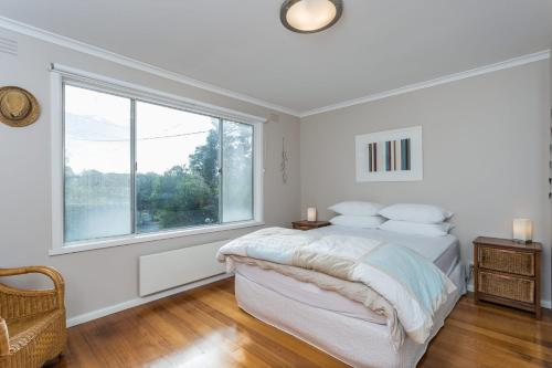 A bed or beds in a room at Orcades Beach House