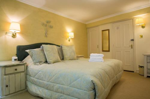 A bed or beds in a room at Cluny Bank Hotel