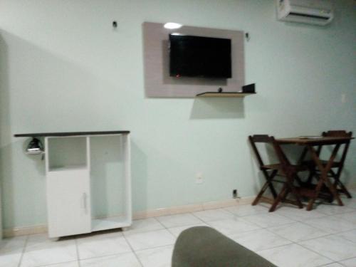 Una televisión o centro de entretenimiento en Ajuricaba Suítes 8