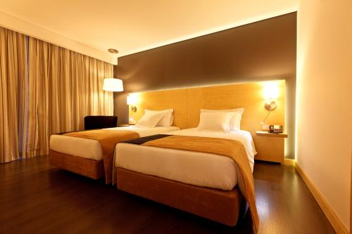 A bed or beds in a room at Hotel Mercure Braga Centro