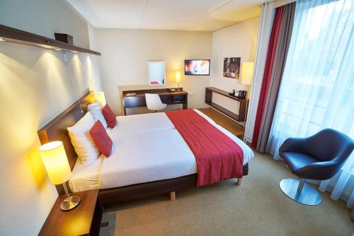 A bed or beds in a room at Amrâth Hotel Media Park Hilversum