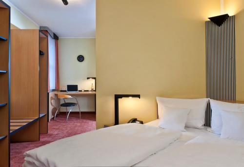 A bed or beds in a room at TRYP by Wyndham Halle