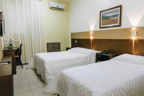 A bed or beds in a room at Aristus Hotel