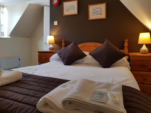 A bed or beds in a room at Old George Hotel