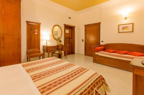 A bed or beds in a room at Mariano IV Palace Hotel
