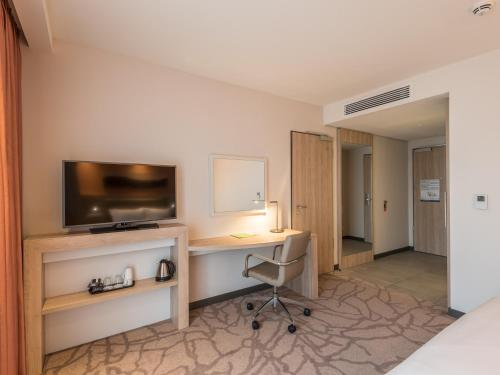 A television and/or entertainment center at Hampton By Hilton Freiburg