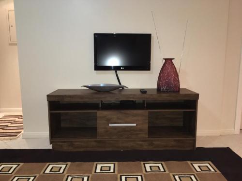 Uma TV ou centro de entretenimento em Excelente Apto 1D c/ Box