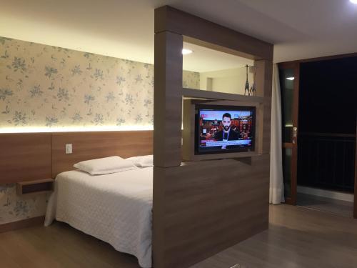 Uma TV ou centro de entretenimento em Loft Em Pedra Azul