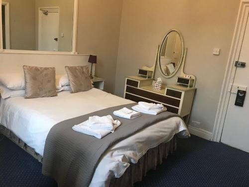 A bed or beds in a room at The Ilchester Arms Hotel