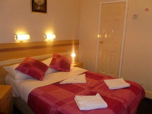 A bed or beds in a room at Grenville House Hotel