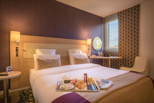 A bed or beds in a room at Mercure Mulhouse Centre