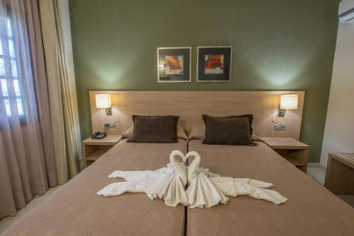 A bed or beds in a room at Relaxia Lanzasur Club - Aqualava Water Park