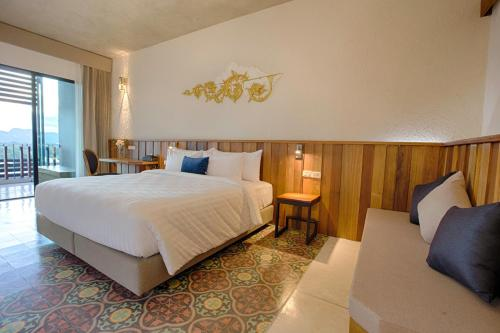 A bed or beds in a room at Natee The Riverfront Hotel Kanchanaburi