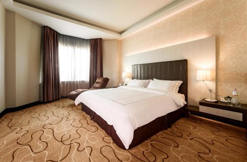 A bed or beds in a room at Promenade Hotel Kota Kinabalu