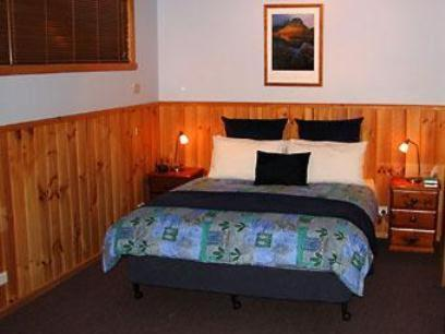 A bed or beds in a room at Derwent Bridge Chalets & Studios